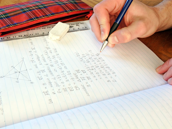 A student's hand doing mathemtics problems in a notebook